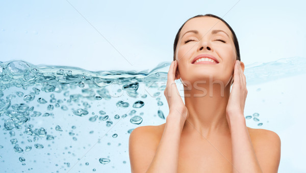 smiling young woman cleaning her face over water Stock photo © dolgachov