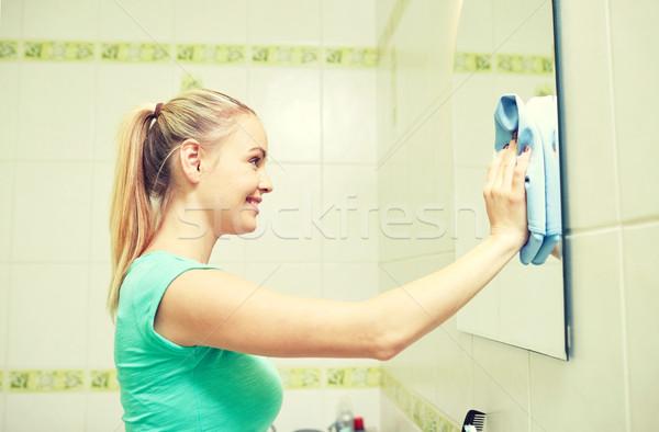 Szczęśliwy kobieta czyszczenia lustra szmata ludzi Zdjęcia stock © dolgachov