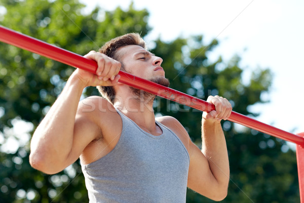 young man exercising on horizontal bar outdoors Stock photo © dolgachov