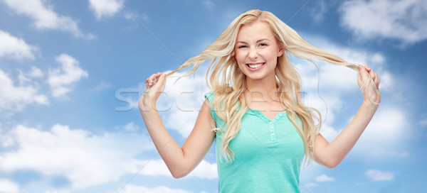 smiling young woman holding strands of her hair Stock photo © dolgachov