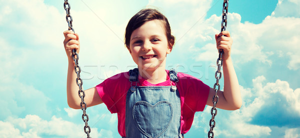 happy little girl swinging on swing over blue sky Stock photo © dolgachov