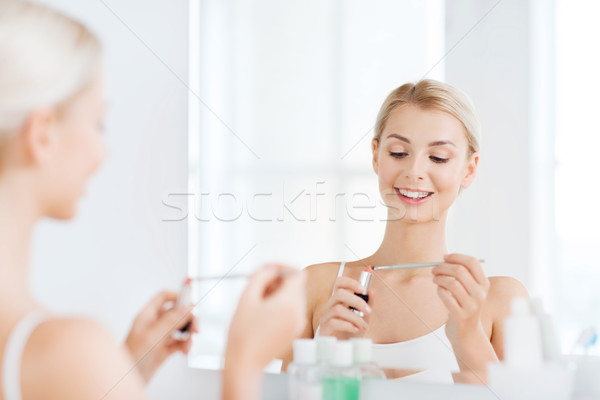 woman with lipstick applying make up at bathroom Stock photo © dolgachov