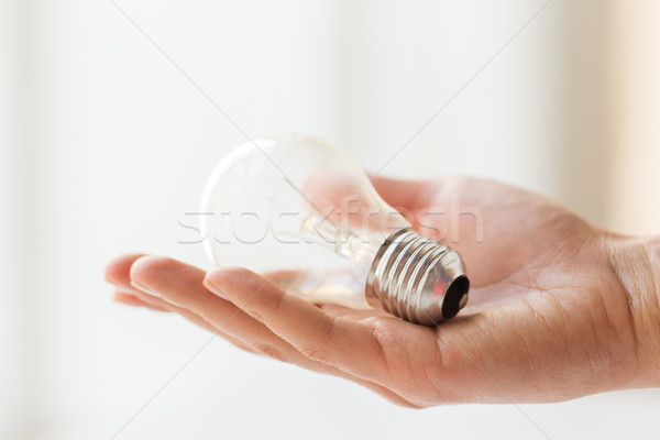 Stock photo: close up of hand holding edison lamp or lightbulb