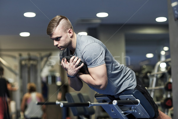 young man flexing back muscles on bench in gym Stock photo © dolgachov