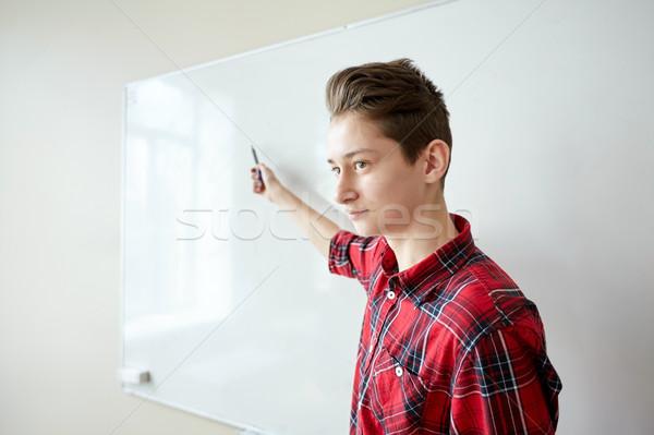 student boy showing something on blank white board Stock photo © dolgachov