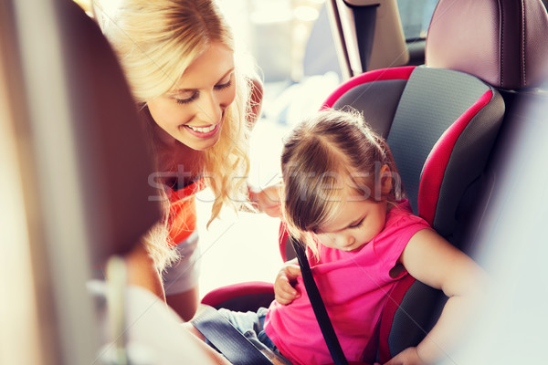 Stock photo: happy mother fastening child with car seat belt