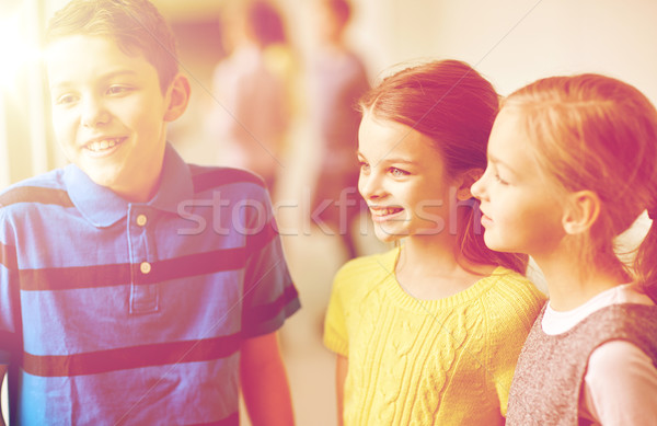 group of smiling school kids talking in corridor Stock photo © dolgachov