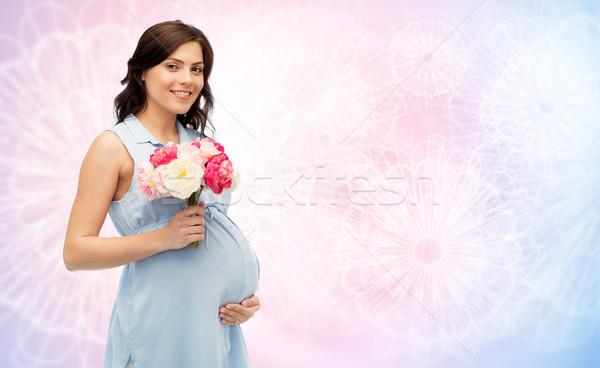 Feliz mulher grávida flores tocante barriga gravidez Foto stock © dolgachov