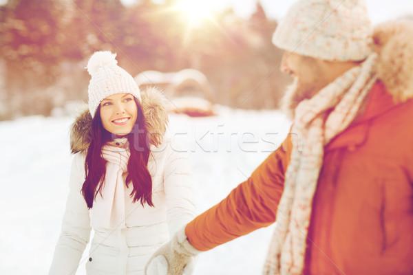 happy couple walking along snowy winter field Stock photo © dolgachov