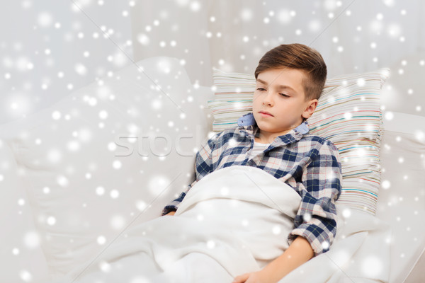 ill boy with flu lying in bed at home Stock photo © dolgachov
