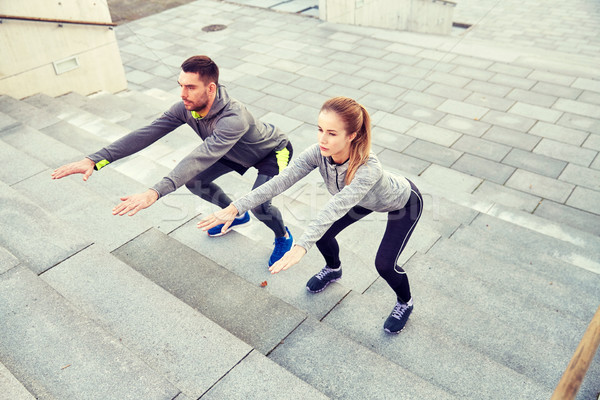 couple doing squats on city street stairs Stock photo © dolgachov