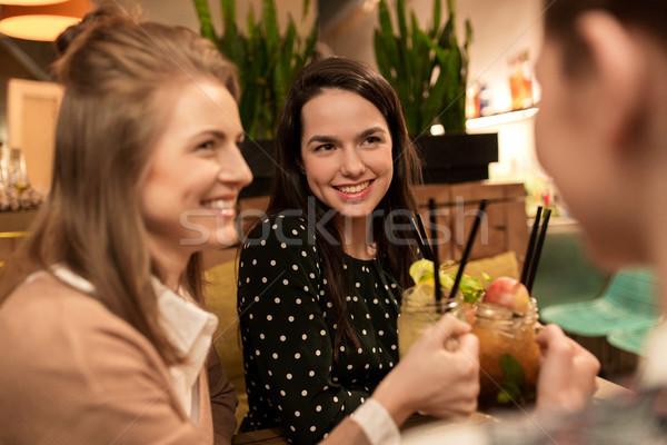 happy friends clinking drinks at restaurant Stock photo © dolgachov