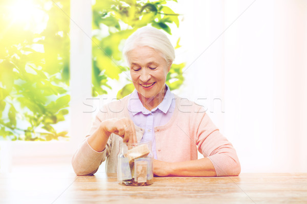 senior woman putting money into glass jar at home Stock photo © dolgachov