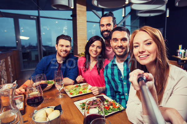 friends picturing by selfie stick at restaurant Stock photo © dolgachov