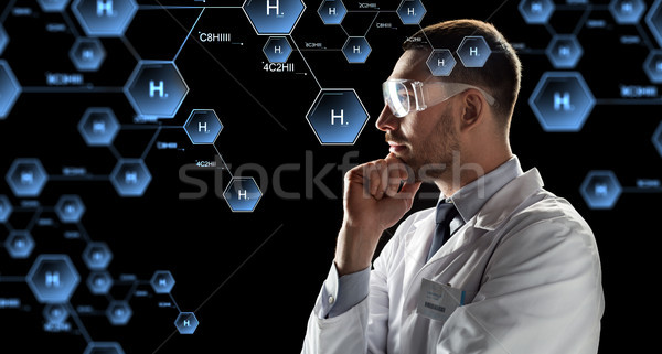 scientist in goggles looking at chemical formula Stock photo © dolgachov