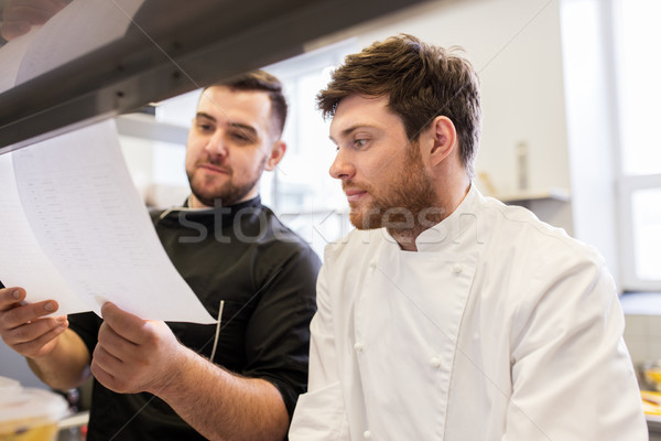 chef and cook with lists or bills at kitchen Stock photo © dolgachov