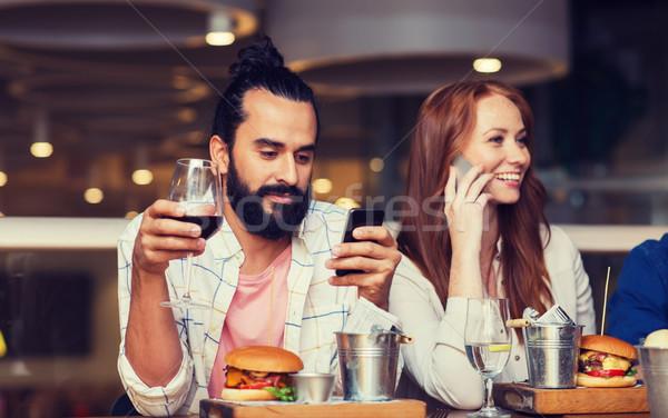 Feliz amigos smartphones restaurante ocio tecnología Foto stock © dolgachov