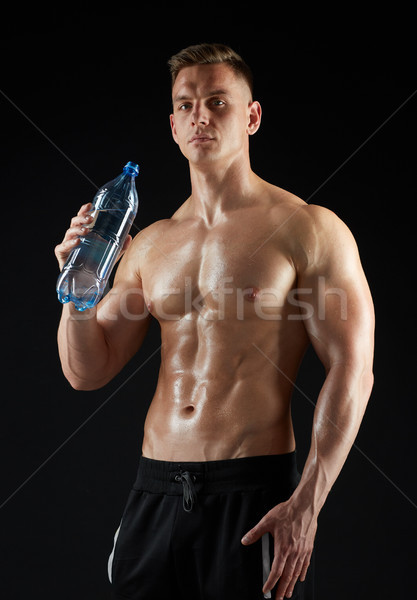young man or bodybuilder with bottle of water Stock photo © dolgachov