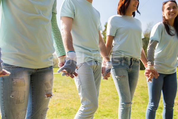 group of volunteers holding hands in park Stock photo © dolgachov