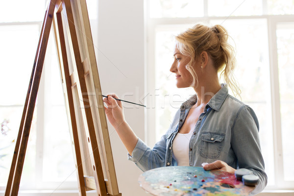 woman artist with easel painting at art studio Stock photo © dolgachov