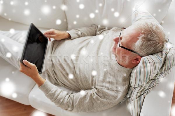 senior man with tablet pc lying on sofa at home Stock photo © dolgachov