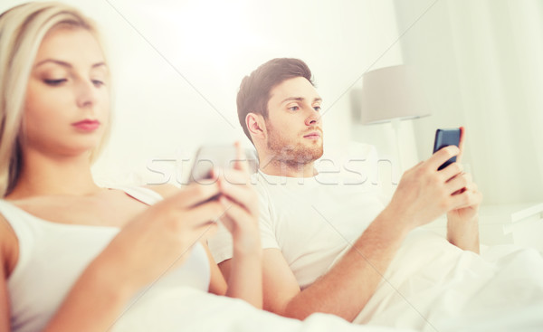 couple with smartphones in bed Stock photo © dolgachov