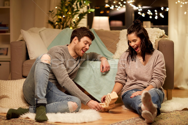 happy couple playing block-stacking game at home Stock photo © dolgachov