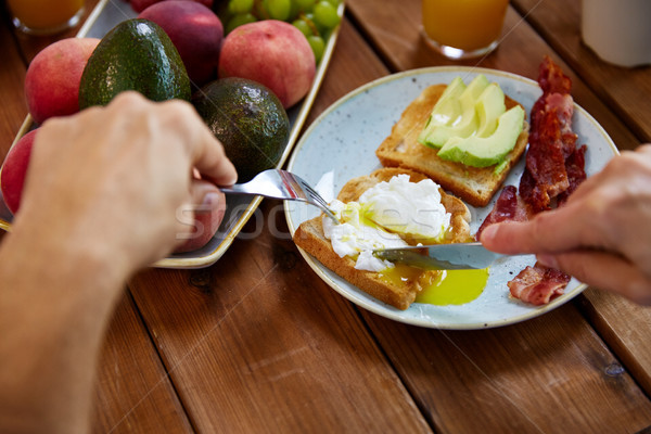 Férfi eszik pirítós tojás szalonna étel Stock fotó © dolgachov