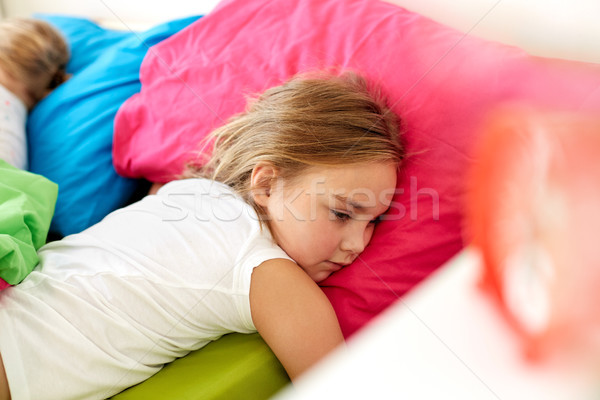 little girl lying awake in bed at home Stock photo © dolgachov