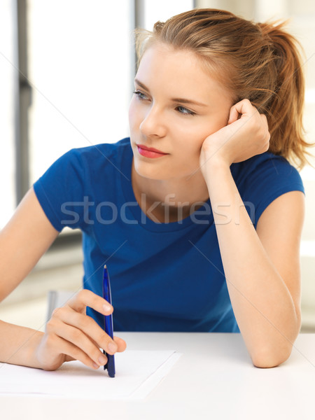 pensive teenage girl with pen and paper Stock photo © dolgachov