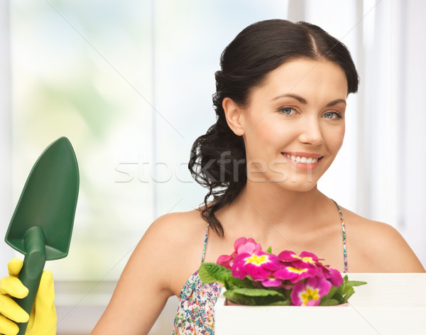 housewife with flower in box and gardening trowel Stock photo © dolgachov