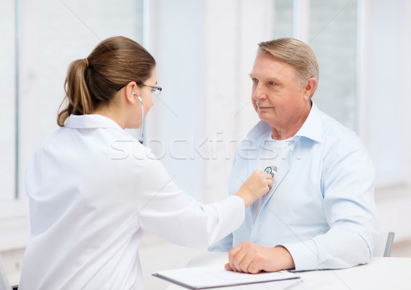 female doctor with old man listening to heart beat Stock photo © dolgachov