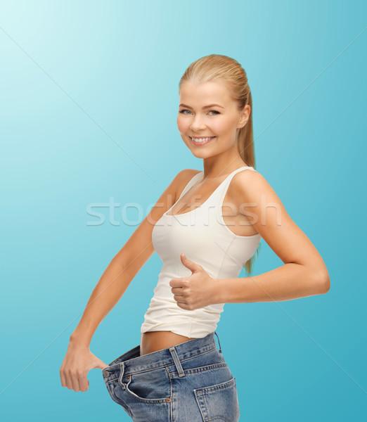 Sportos nő mutat nagy nadrág fitnessz Stock fotó © dolgachov