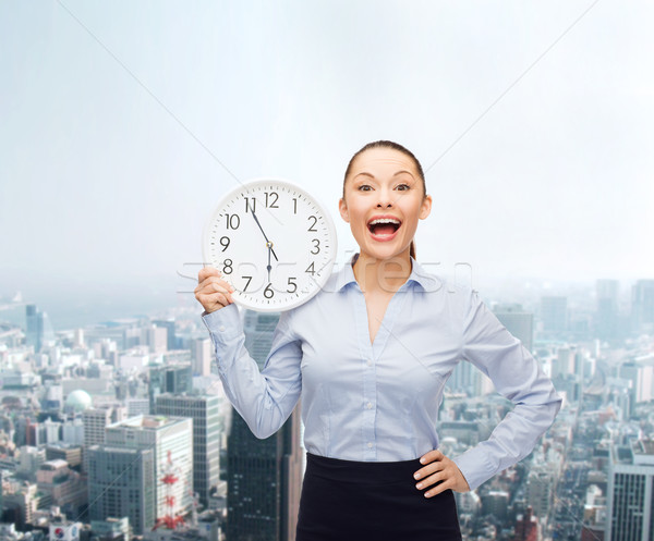 attractive businesswoman with wall clock Stock photo © dolgachov