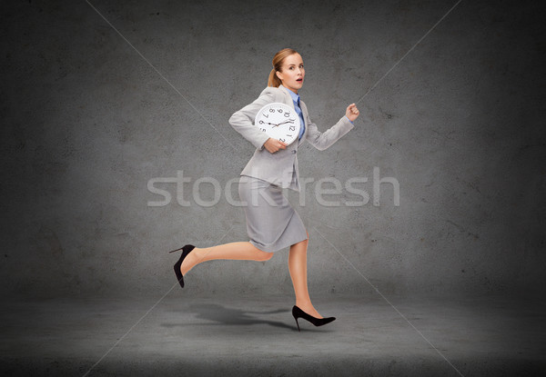 stressed young businesswoman with clock running Stock photo © dolgachov