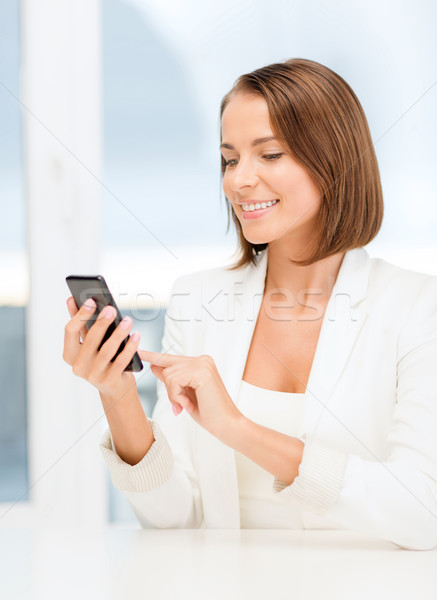 smiling businesswoman browsing in smartphone Stock photo © dolgachov