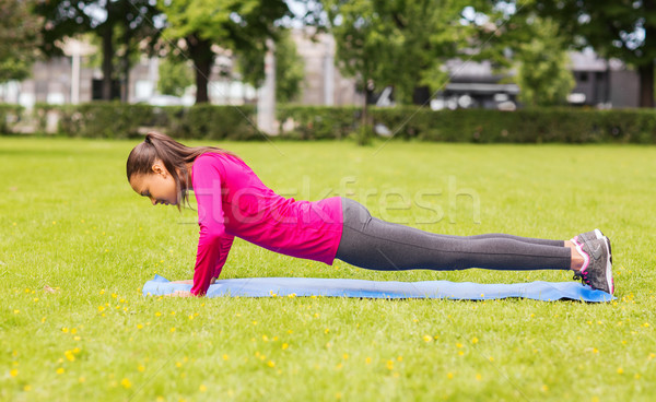 smiling woman doing doing push-ups on mat outdoors Stock photo © dolgachov
