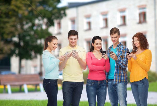 Csoport mosolyog tinédzserek okostelefonok barátság technológia Stock fotó © dolgachov