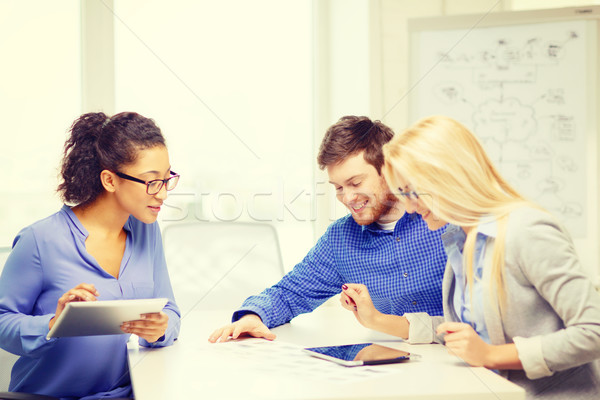 smiling team with table pc and papers working Stock photo © dolgachov