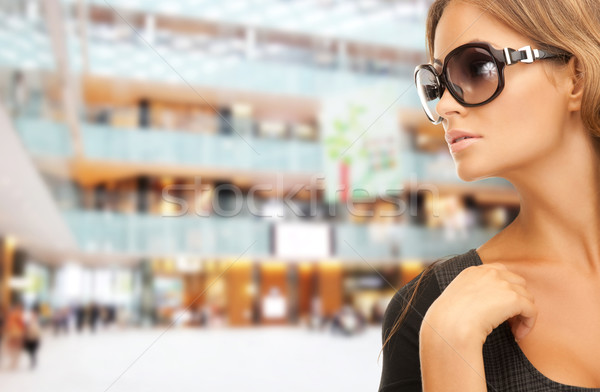 beautiful woman in shades over mall background Stock photo © dolgachov