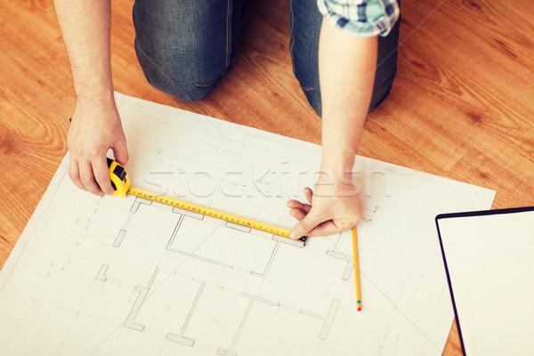 close up of male hands measuring blueprint Stock photo © dolgachov