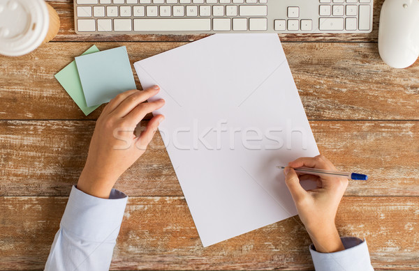 close up of hands with paper sheet and keyboard Stock photo © dolgachov