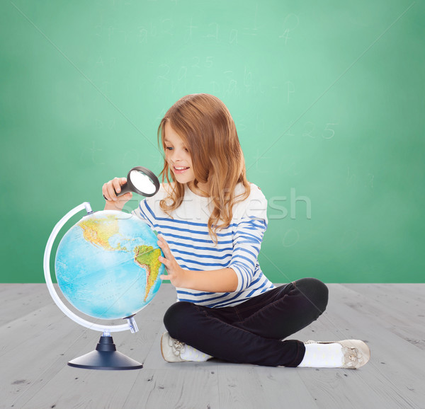 happy girl looking at globe with magnifier Stock photo © dolgachov