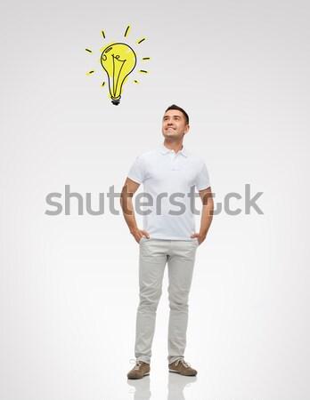 smiling man pointing finger to lighting bulb Stock photo © dolgachov