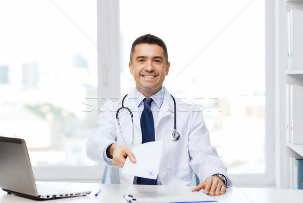 happy doctor with prescription and laptop Stock photo © dolgachov