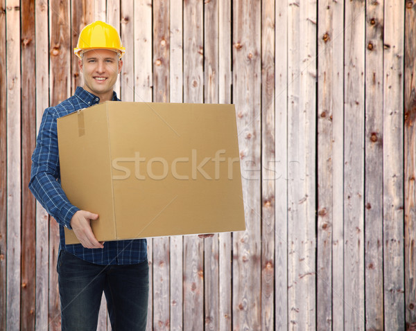smiling male builder in helmet with cardboard box Stock photo © dolgachov