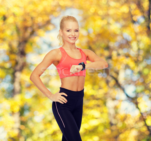 smiling woman with heart rate monitor on hand Stock photo © dolgachov