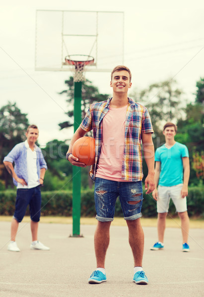 group of smiling teenagers playing basketball Stock photo © dolgachov