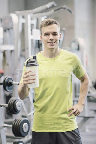Sorridente homem proteína tremer garrafa esportes Foto stock © dolgachov