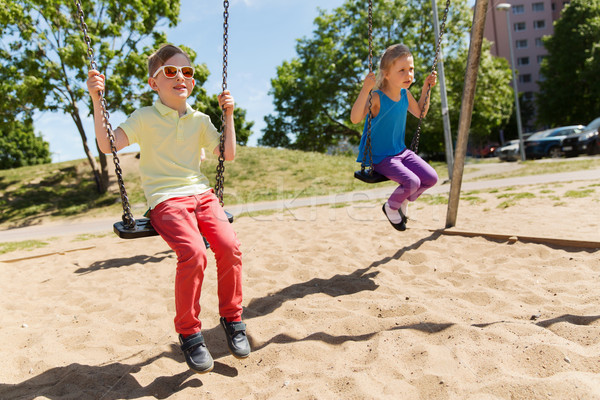 two happy kids swinging on swing at playground Stock photo © dolgachov